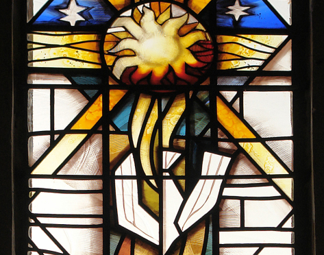 The Lord represented by the Sun with rays of light emanating from the centre of the sun in a cross motif as part of the stained glass West Window at St. David's Church, Newbold on Stour by glass artist Derek Hunt FMGP