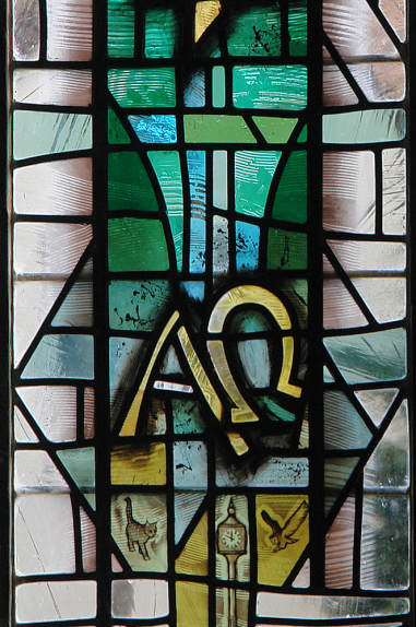 St. Barbara's Church, Earlsdon detail from lower left lancet using palette of rich and pale greens on a background of clear antique glass depicting the symbols of Alpha and Omega by stained glass artist Derek Hunt FMGP