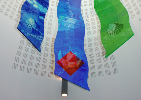 "Saint Felix Roman Catholic Church, Haverhill ""The Waters of Baptism"" Artist's impression of a hanging glass sculpture, using 10mm silicon acrylic glass complete with digital printing, suspended on thin steel wires. The abstract design uses a translucent arrangement of subtle blues an greens to allude to the Baptism of Christ with images of the Holy Spirit in the form of a dove descending, undulating text based on Mathew 3:16, the blue waters of baptism and the shell used by John the Baptist. And Behold, the Heavens opened up and the Spirit of the Lord descended like a dove. St Felix Church, Haverhill - architectural glass design by glass artist Derek Hunt FMGP"