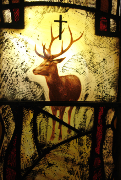 Focal point of stained glass window design by glass artist Derek Hunt showing detail of central cross with a stag on painted muted yellow and grey background